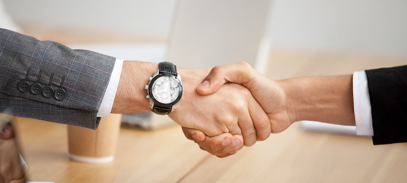 Close up view of handshake, two businessmen in suits shaking hands as concept of trust, good partnership deal, signing contract agreement at meeting, gratitude for help support in business